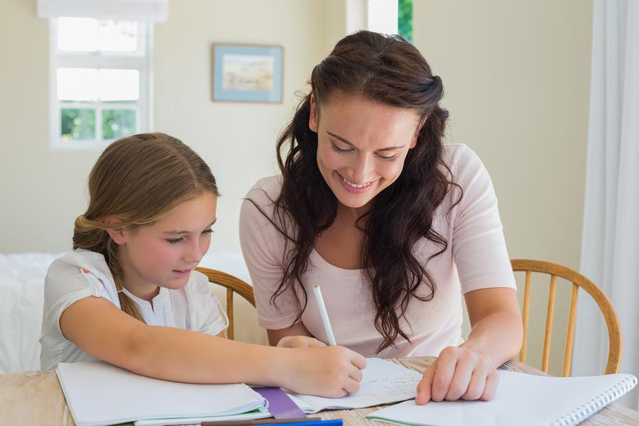 Woman helping daughter in homework at table